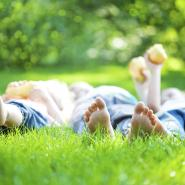 three kids laying in the grass on their backs