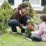 Mother and daughter gardening in green, healthy lawn